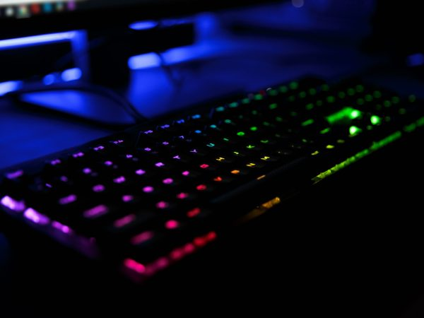 Close up view of workplace with led rainbow backlight gaming usb keyboard of computer lying on table in dark room