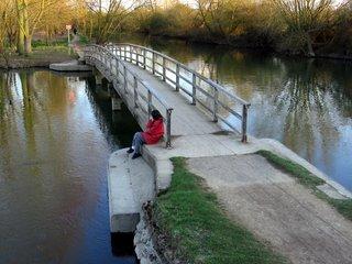 Woman beside bridge beside Port Meadow