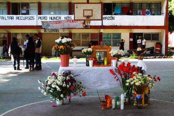 En el centro de la cancha de la Escuela Normal de Ayotzinapa hay un altar con santos y veladoras. Foto: Antonio Cruz, SinEmbargo.