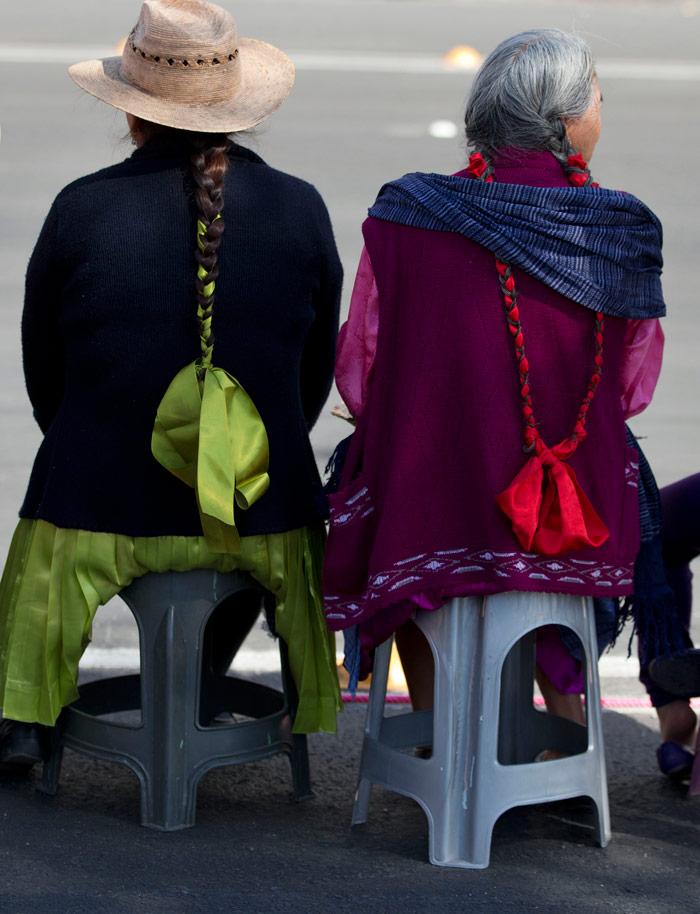 Mujeres indígenas sentadas en taburetes mientras esperaban a que el Papa Francisco pasara en su camino hacia la Basílica de la Virgen de Guadalupe, en Ciudad de México, el sábado 13 de febrero. Foto: Rebecca Blackwell, AP