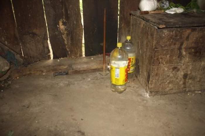 En la imagen se observan un par de botellas que don Macario utiliza para recolectar agua pluvial. Están en el piso, misma superficie que vio nacer y morir a sus hijos. Foto: BlogExpediente.