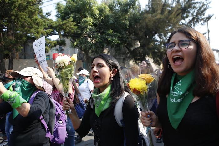 Mujeres lanzan consignas con flores en las manos mieNtras se dirigen al edificio de apartamentos en que Ingrid Escamilla fue asesinada y desollada, en Ciudad de México, el sábado 15 de febrero de 2020. Foto: Ginnette Riquelme, AP