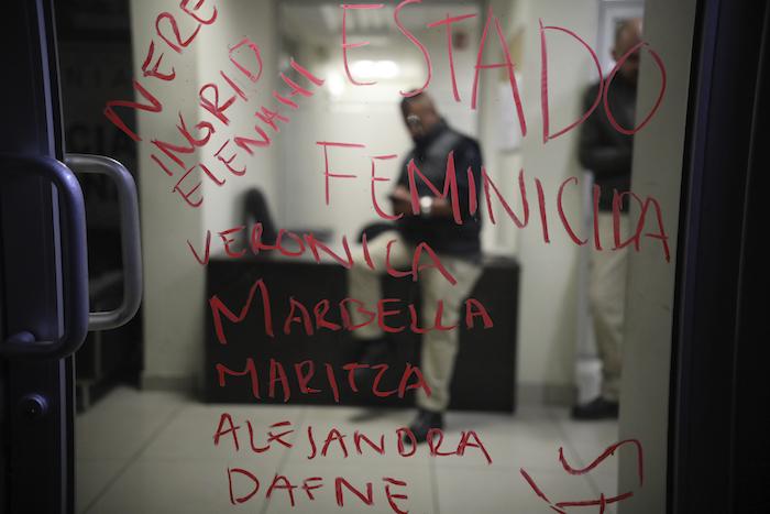 """Las palabras """"Estado feminicida"""" y una lista de nombres de mujeres asesinadas, escrita con pintalabios en la puerta de la fiscalía, con varios policías al otro lado. La pintada quedó tras una protesta contra la violencia de género en Tijuana, México, el sábado 15 de febrero de 2020. Foto: Emilio Espejel, AP"""