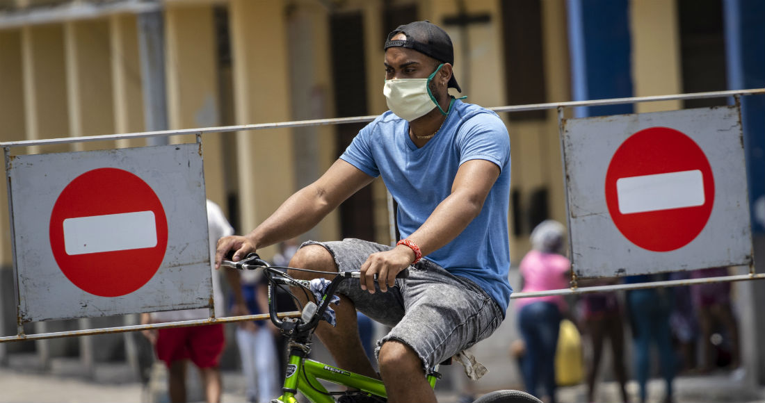 Un hombre con una mascarilla para evitar el contagio del nuevo coronavirus cruza en bicicleta los letreros que prohíben la entrada de vehículos en una zona donde ha aumentado el número de personas infectadas con COVID-19 en el centro de La Habana, Cuba, el sábado 9 de mayo de 2020.