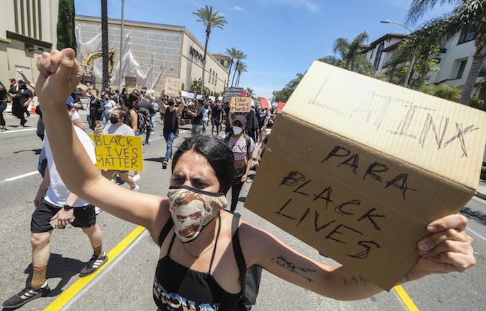 Una mujer sostiene un cartel durante una protesta por la muerte de George Floyd, en Los Ángeles, el sábado 30 de mayo de 2020. En todo Estados Unidos se registraron crecientes protestas tras la muerte de George Floyd, que murió tras ser reducido por policías de Minneapolis el 25 de mayo de 2020.