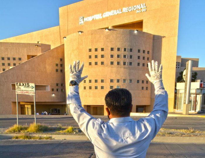 Con sus manos en alto, un hombre realiza una oración frente al Hospital General Regional 66 del IMSS, donde se concentra el mayor número de pacientes con COVID-19 en Ciudad Juárez.