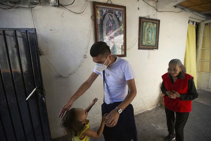 El doctor Juan Antonio Salas, en el centro, bromea con la nieta de su paciente Cleotilde Borja, una sobreviviente de COVID-19, justo al final de su visita médica voluntaria a su hogar en la Ciudad de México, el viernes 5 de junio de 2020.