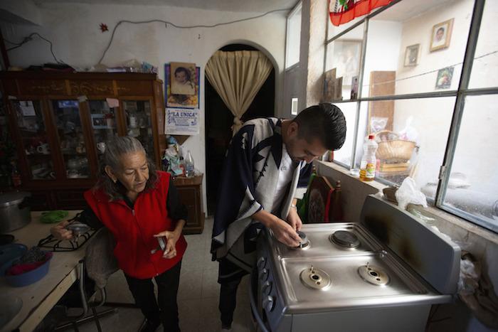 El doctor Juan Antonio Salas ayuda a la sobreviviente de COVID-19 Cleotilde Borja con su estufa en su casa en la Ciudad de México, el viernes 5 de junio de 2020.
