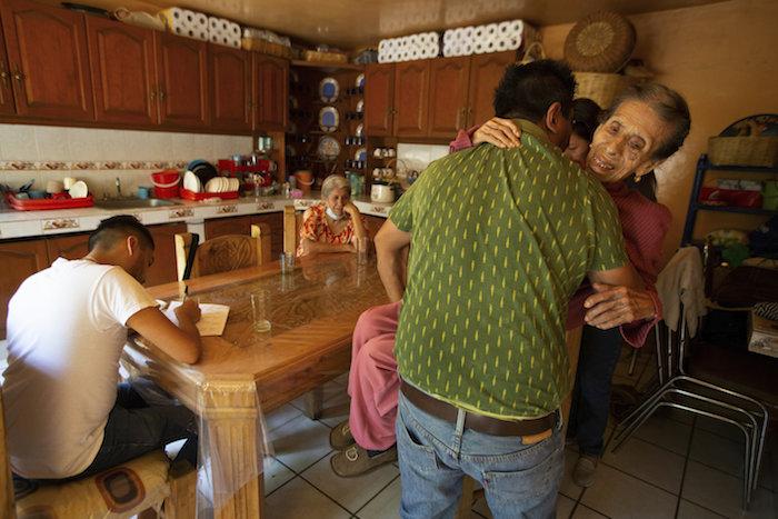 Orlando Infante lleva a su madre Beatriz Infante, una sobreviviente de COVID-19, a una silla de ruedas después de una visita médica de seguimiento del doctor Juan Antonio Salas, sentado a la izquierda, en su casa en la Ciudad de México, el viernes 5 de junio de 2020.