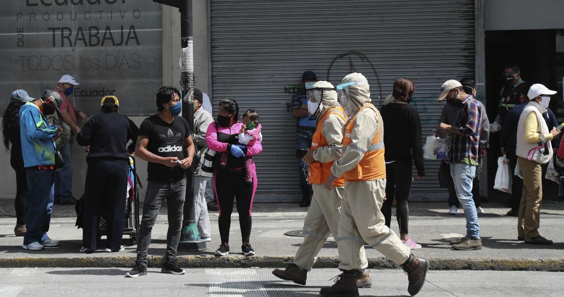 Trabajadores con trajes de protección para prevenir el nuevo coronavirus caminan junto a peatones en Quito, Ecuador, el miércoles 10 de junio de 2020.