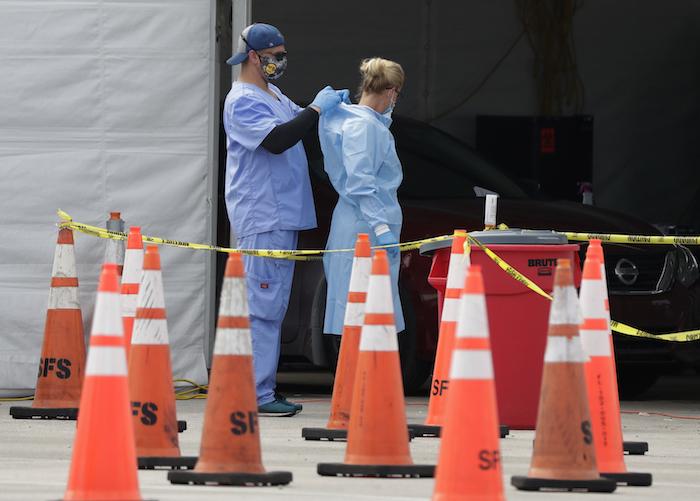Trabajadores de la salud se ayudan mutuamente a colocarse equipo protector en un sitio de testeo del coronavirus en Miami Gardens, Florida, 5 de julio de 2020. El equipo protector para los trabajadores que atienden a enfermos de COVID-19 vuelve a escasear.