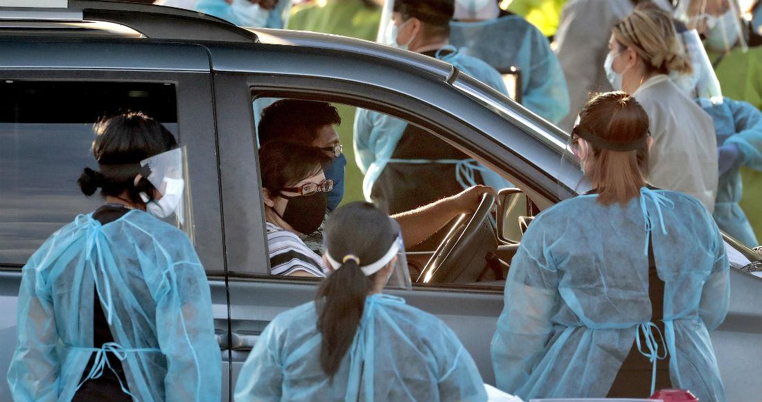 Una familia detiene la marcha de su vehículo en un centro de pruebas gratuitas de COVID-19 desde el auto en el vecindario de Maryvale, en el oeste de Phoenix, Arizona, el sábado 27 de junio de 2020.