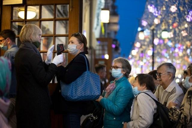 Unas personas con cubrebocas debido al coronavirus se forman para entrar al teatro Chekhov'v en el centro de Moscú, Rusia, el 25 de septiembre de 2020.