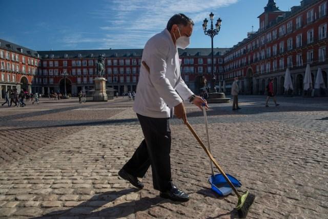 Un mesero porta una mascarilla para evitar la propagación del coronavirus mientras barre la terraza de un bar en el centro de Madrid, España, el viernes 9 de octubre de 2020.