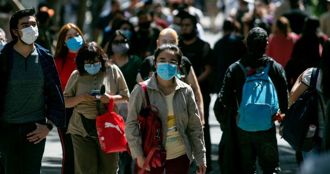 Un grupo de personas camina por calles de la Ciudad de México durante la contingencia sanitaria por la COVID-19.