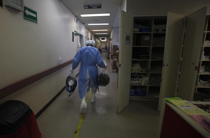 Un trabajador de salud lleva la ropa de los pacientes con COVID-19 que se han recuperado de la enfermedad y están siendo dados de alta del Hospital General Ajusco Medio de la Ciudad de México, el miércoles 2 de diciembre de 2020.