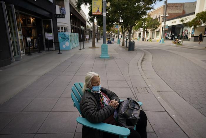 Esta fotografía muestra a Margaret Speck, de 77 años, sentada en una calle comercial vacía en Santa Mónica, California, el martes 8 de diciembre de 2020.