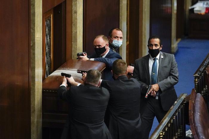 Policías del Capitolio federal apuntan sus armas cerca de una puerta con una barricada mientras unos manifestantes tratan de ingresar al recinto de la Cámara de Representantes, en Washington, el miércoles 6 de enero de 2021.
