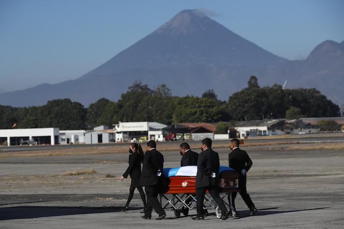 Personas transportan un ataúd cubierto con banderas en la pista mientras los restos de 16 migrantes guatemaltecos que murieron cerca de la frontera entre Estados Unidos y México en enero llegan a la base de la Fuerza Aérea en la Ciudad de Guatemala, el viernes 12 de marzo de 2021.