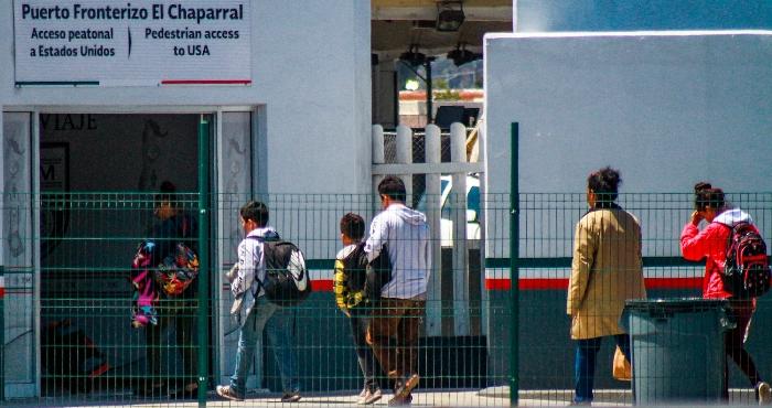 Migrantes centroamericanos cruzan hacia Estados Unidos por la línea ubicada en la ciudad del El Chaparral, en la fronteriza Tijuana (México).