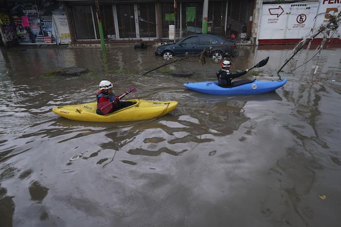 Una pareja navega sus kayaks por una calle inundada en Tula, en el estado de Hidalgo, México, el martes 7 de septiembre de 2021.