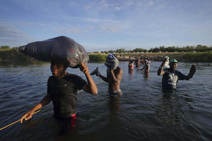 Migrantes, muchos de Haití, cruzan el Río Bravo mientras abandonan Del Río, Texas, para regresar a Ciudad Acuña, México, el miércoles 22 de septiembre de 2021 temprano, algunos para evitar una posible deportación de EU otros a conseguir suministros.