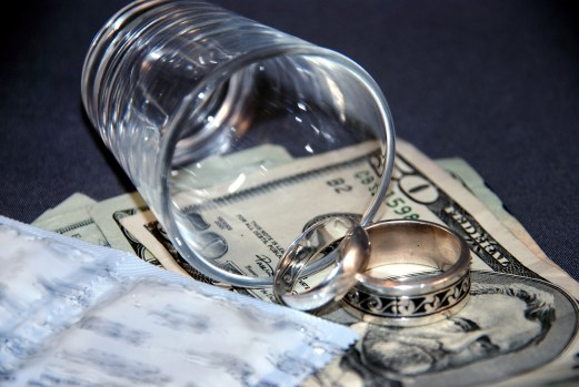 money, wedding rings, shot glass