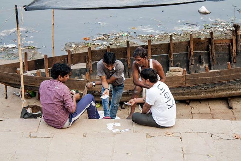 Cuatro amigos jugando a las cartas a orillas del sucio pero sagrado río Ganges