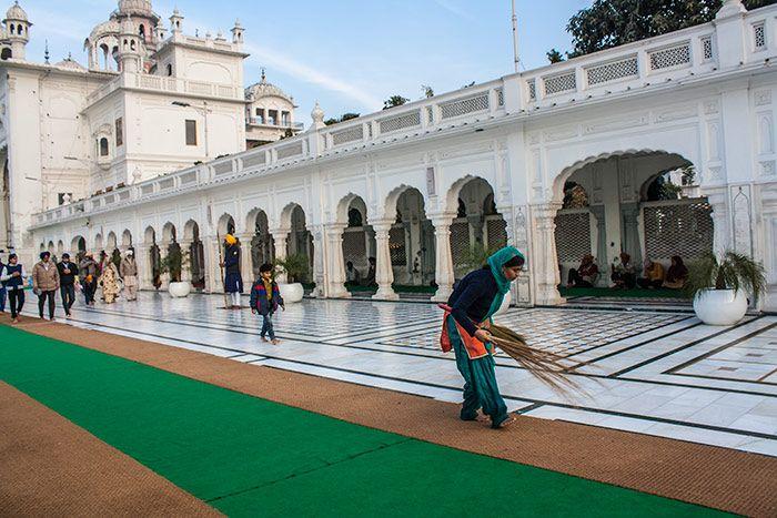 Mujer limpiando la galeria alrededor del Templo Dorado