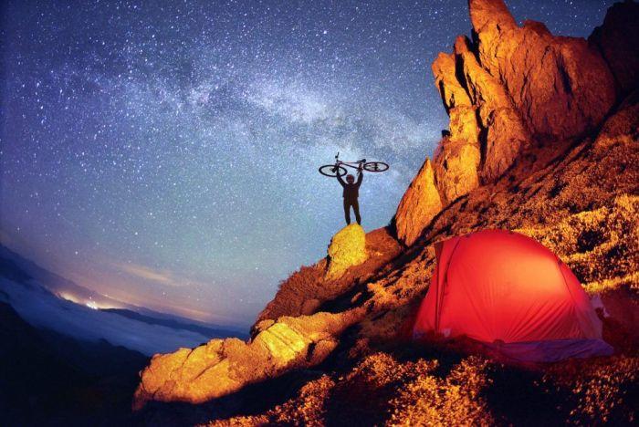 En la cima del mundo, con la bici y la tienda de campaña vía Shutterstock