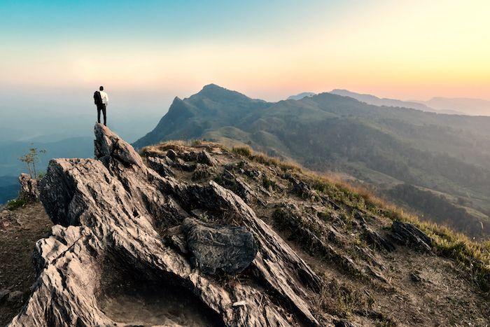 Hombre parado en la cima del mundo