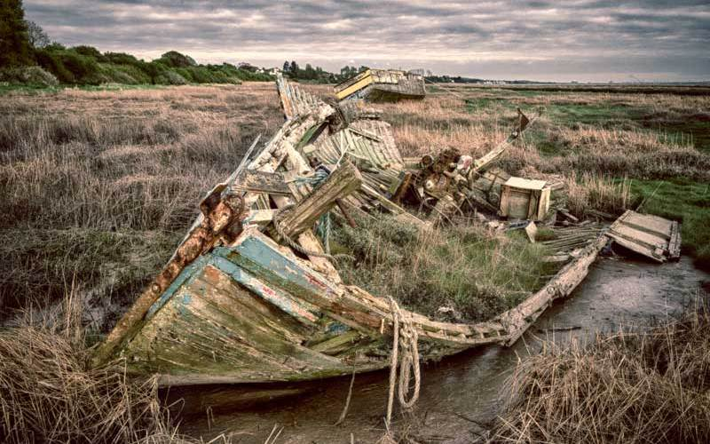 A boat gradually decays, doomed to remain on the foreshore