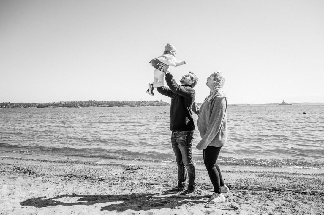 Perhe leikkimässä meren rannalla