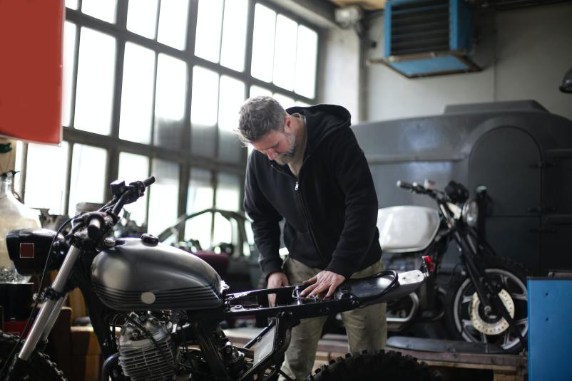 serious adult male mechanic repairing motorbike in garage 3855224
