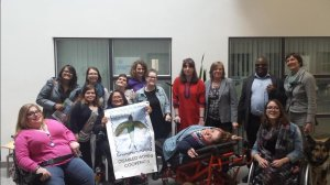 Photo of participants with disabled women and one man, wheelchair user carrying sister of Frida banner.