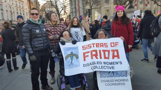 Group of women, 2 wheelchair users holding a banner with words 'Sisters of Frida Disabled Women's Collective, four other women standing behind