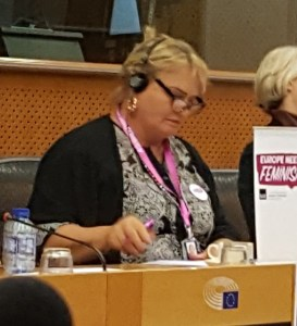 woman with blonde hair and black rimmed glasses. She has a notice that says Feminism in Europe