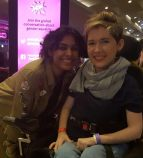 Sarah Rennie, a young looking blonde short haired wheelchair user with an Asian young looking woman next to her. behind them is a bright pink WOW sign in lights/