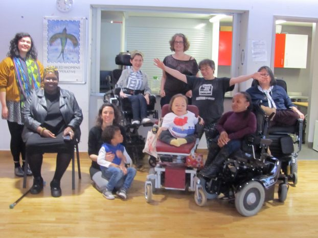 group of 9 women, 4 are wheelchair users. There is a male child of mixed heritage. here are 2 East Asians and 2 black women. one woman had both her hands out in an embracing gesture