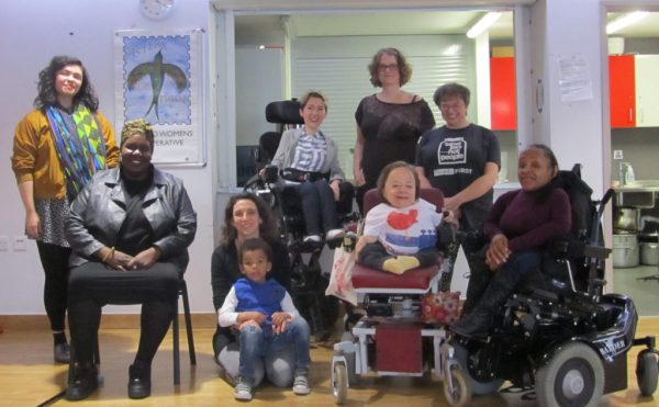 Women in a group, one black woman seated on a chair, 3 wheelchair users and one women with arms spread out.