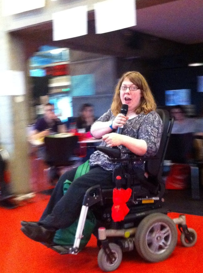 young white woman wheelchair user holding a microphone. She has long brown hair and the flooring is brilliant red while the other people are in a blur.
