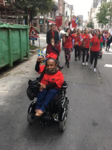 Michelle (wearing the red tee ENIL teeshirt) with her hand raised up in a fist leading some of the procession