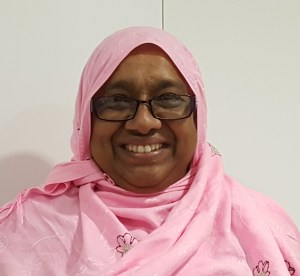 asian woman in pink with glasses smiling