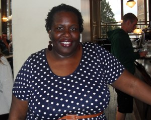 black woman smiling in blue and white polka dress in a pub type environment