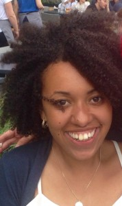 young black woman smiling broadly into camera with fuzzy hair.