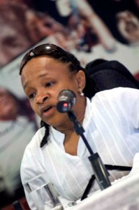Black woman in front of a mic - shes wearing a white shirt.