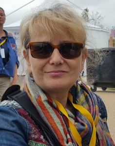 white woman with blonde hair tied back and wearing sun glasses. she has a colourful scarf.