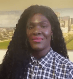 Black woman with long hair and red lipstick. shes wearing a check shiret.