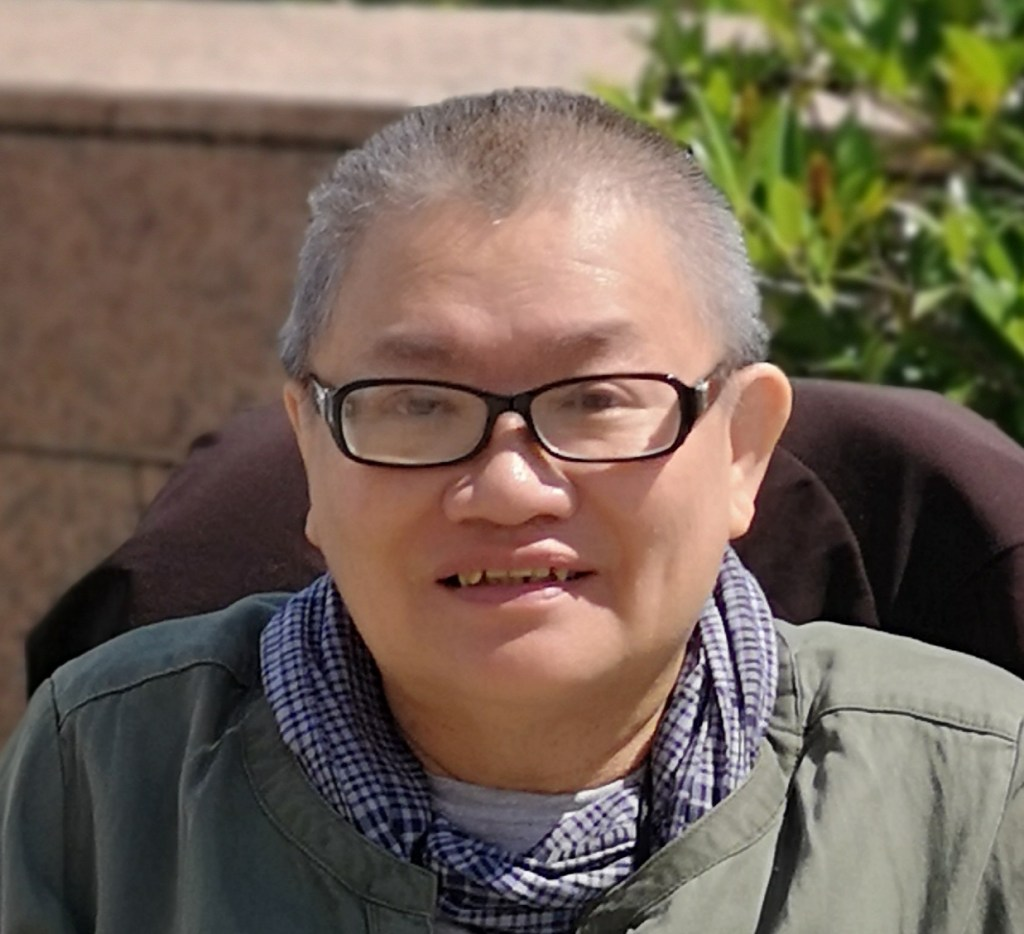 East Asian woman with clipped hair and glasses