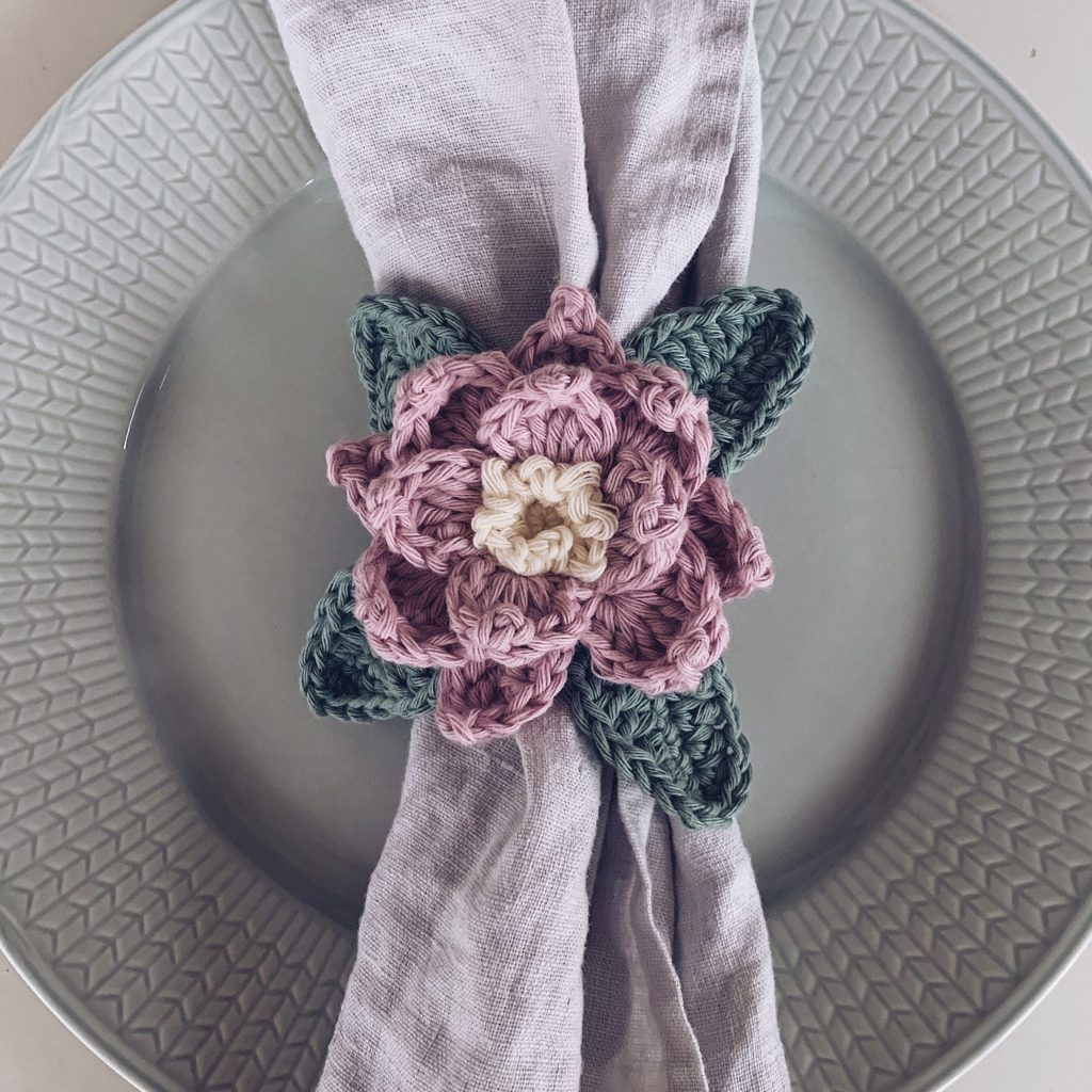 A Crocheted Pretty Poinsettia Napkin ring in soft pink, yellow and green colors are placed around a light grey linen cloth onto of a light green plate